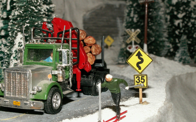 A log truck passes a cross country skiier on a snow covered road