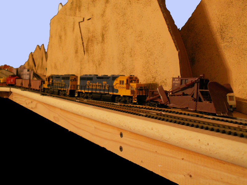 A maintaince of way train heads out to work with a spreader on the point and three balast hoppers behind a pair of GP40 locomotives